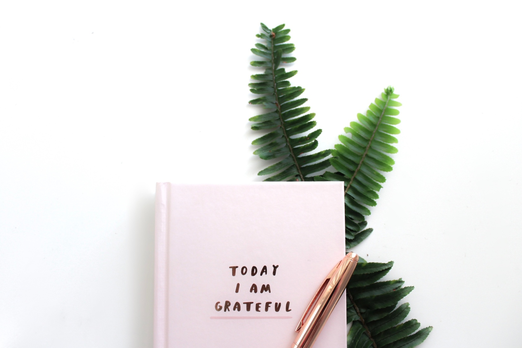 """Pink notebook and pen that says """"Today I am Grateful."""""""
