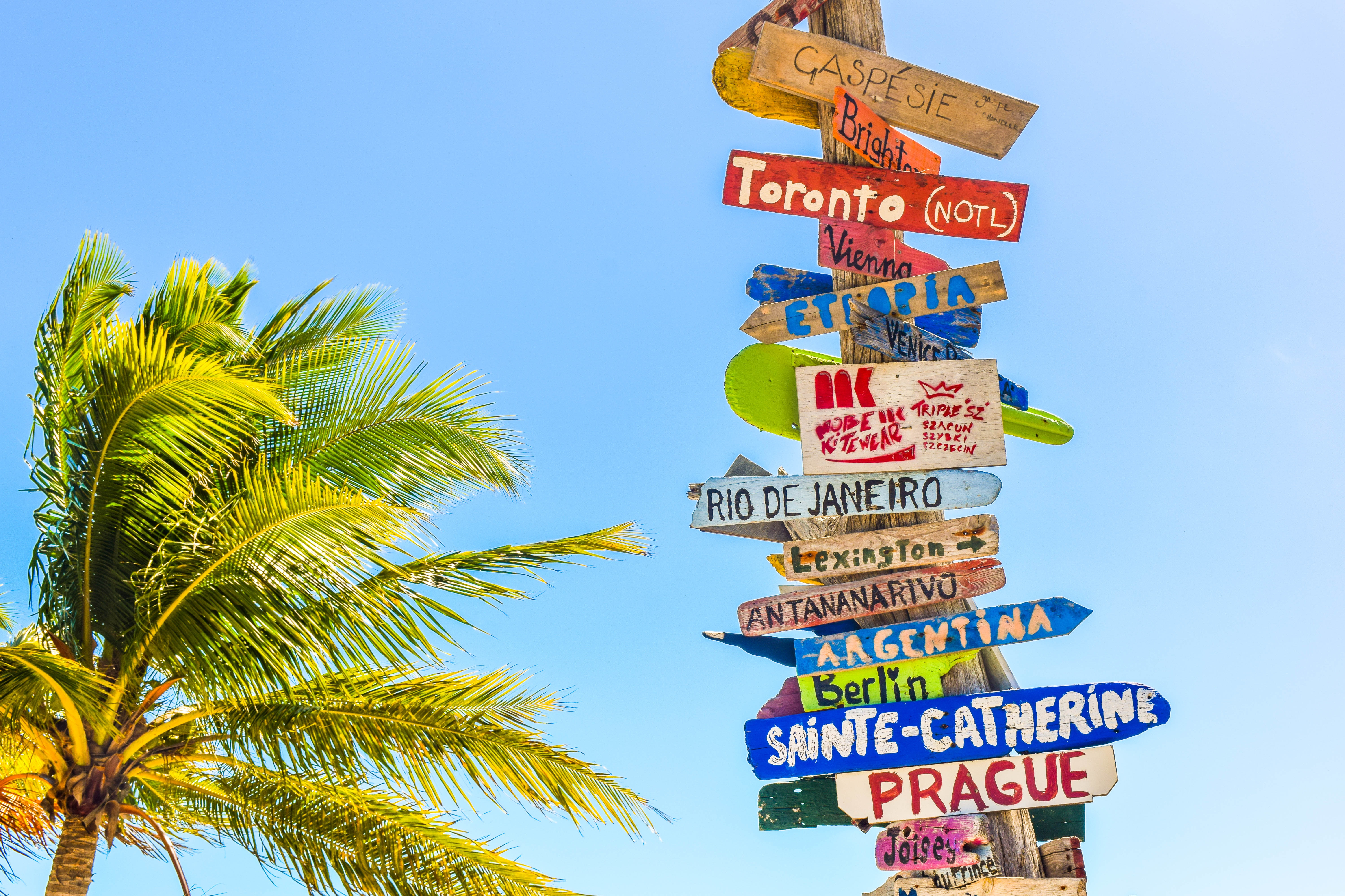 Photo of a pole with many wooden signs pointing to vacation spots like Rio De Janeiro, Prague, and Toronto.
