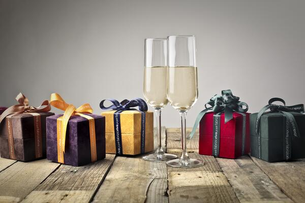 Photo of finely wrapped client gifts with a couple of classes of white wine.