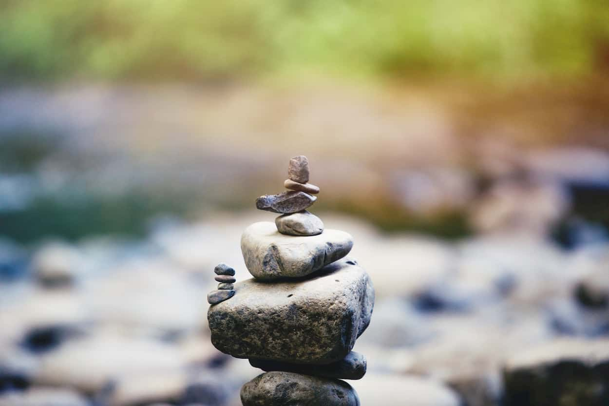 Photo of river stones balancing on top of each other to represent wellness.