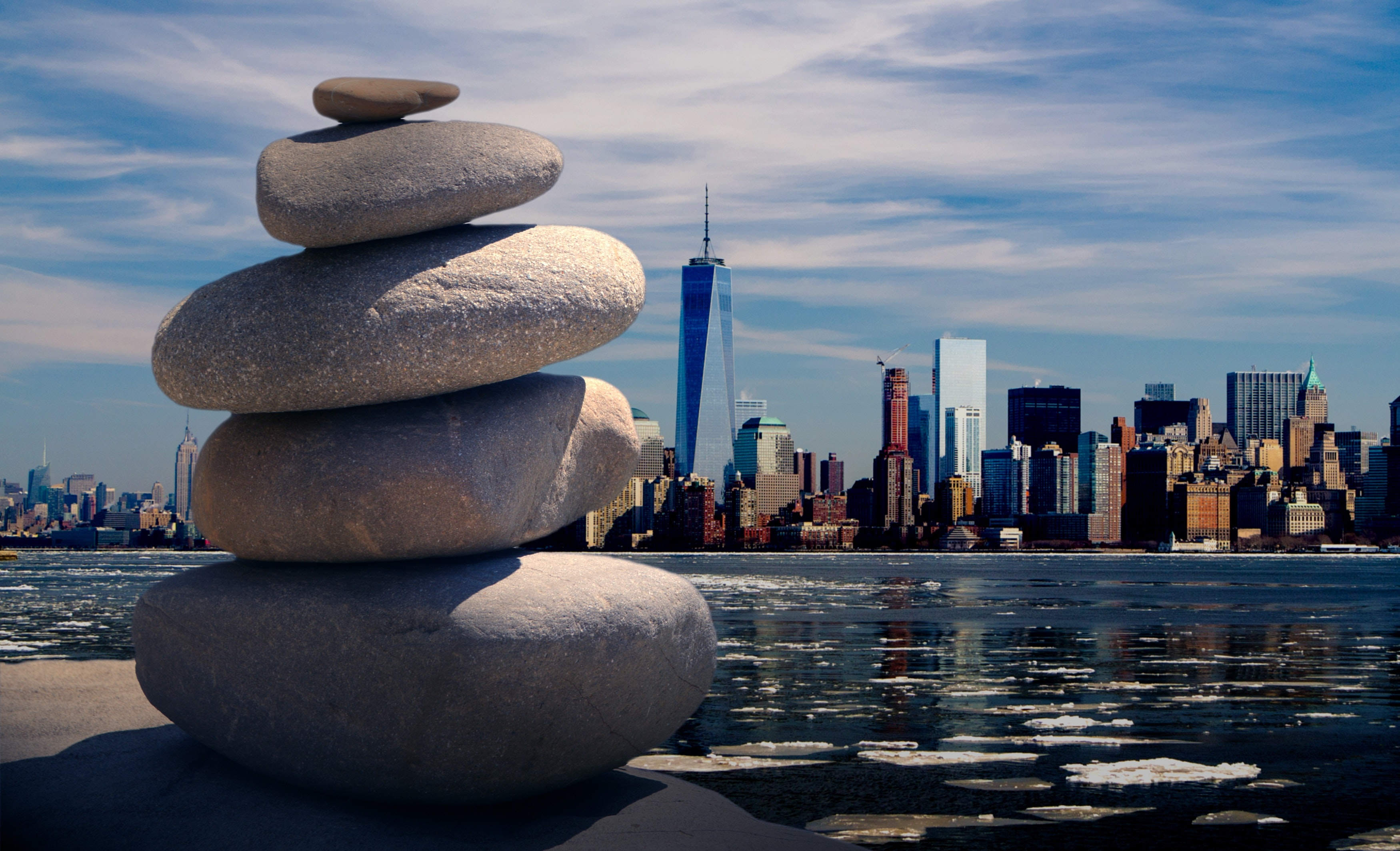 stones balanced on top of one another in front of a city skyline to represent work-life balance.