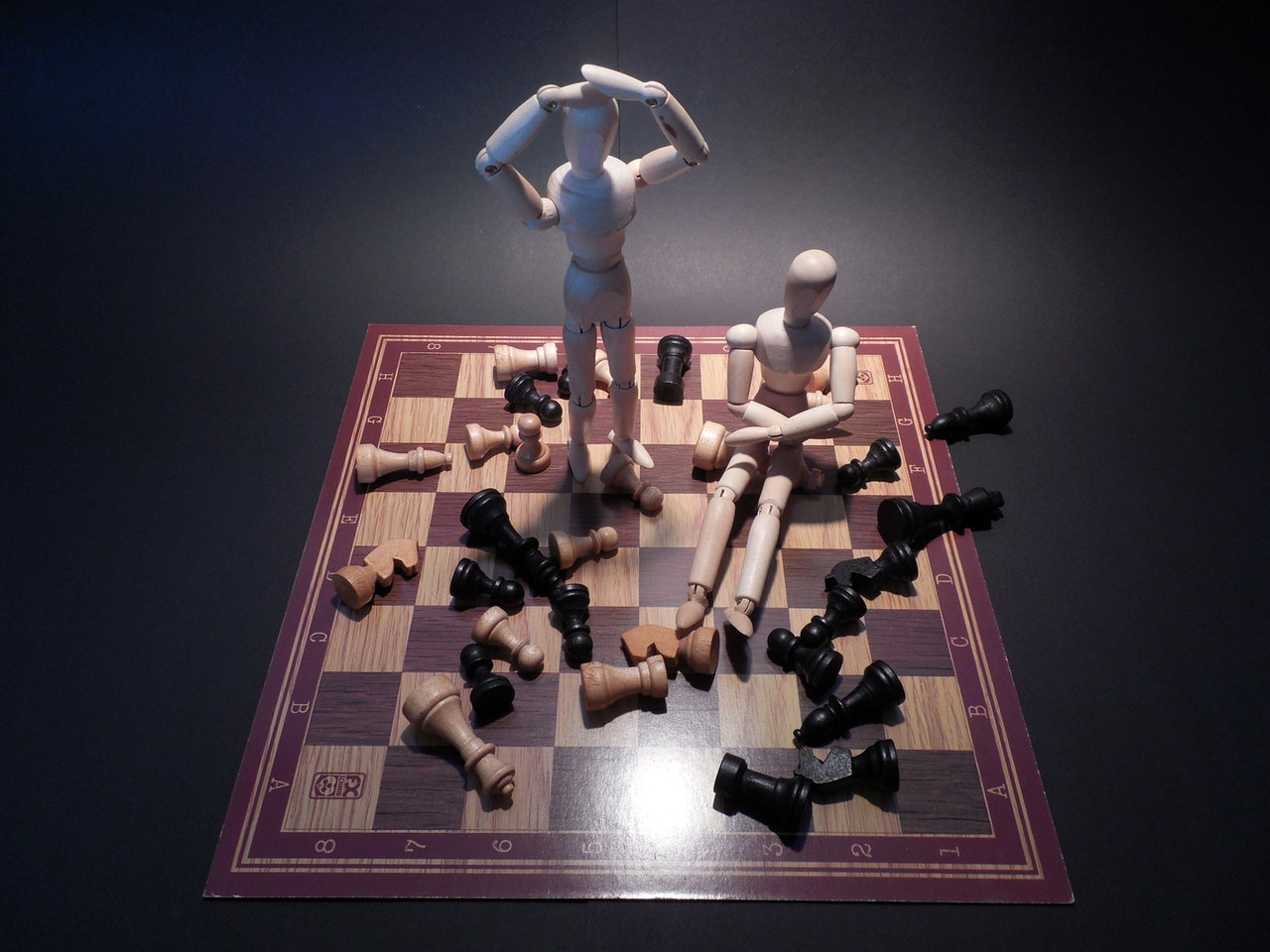 Photo of chess board with all the pieces knocked over and two wooden human figurines with their hands on their head trying to figure out how to overcome their mistakes.