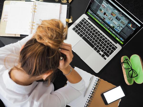 Photo of woman sitting at a desk and struggling with workplace stress.