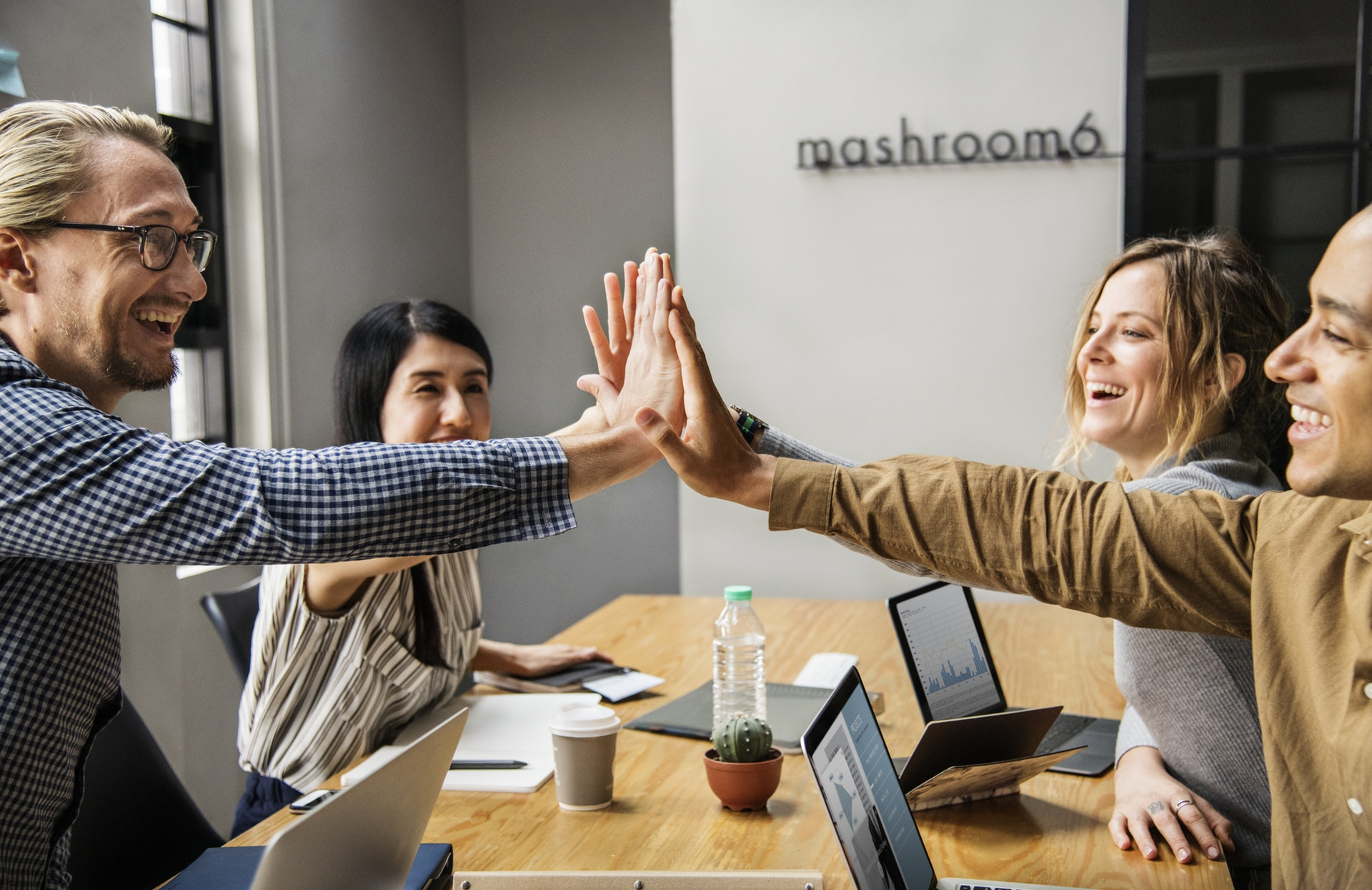 Photo of four top performing employees high-fiving because they're happy with their company's employee retention strategies
