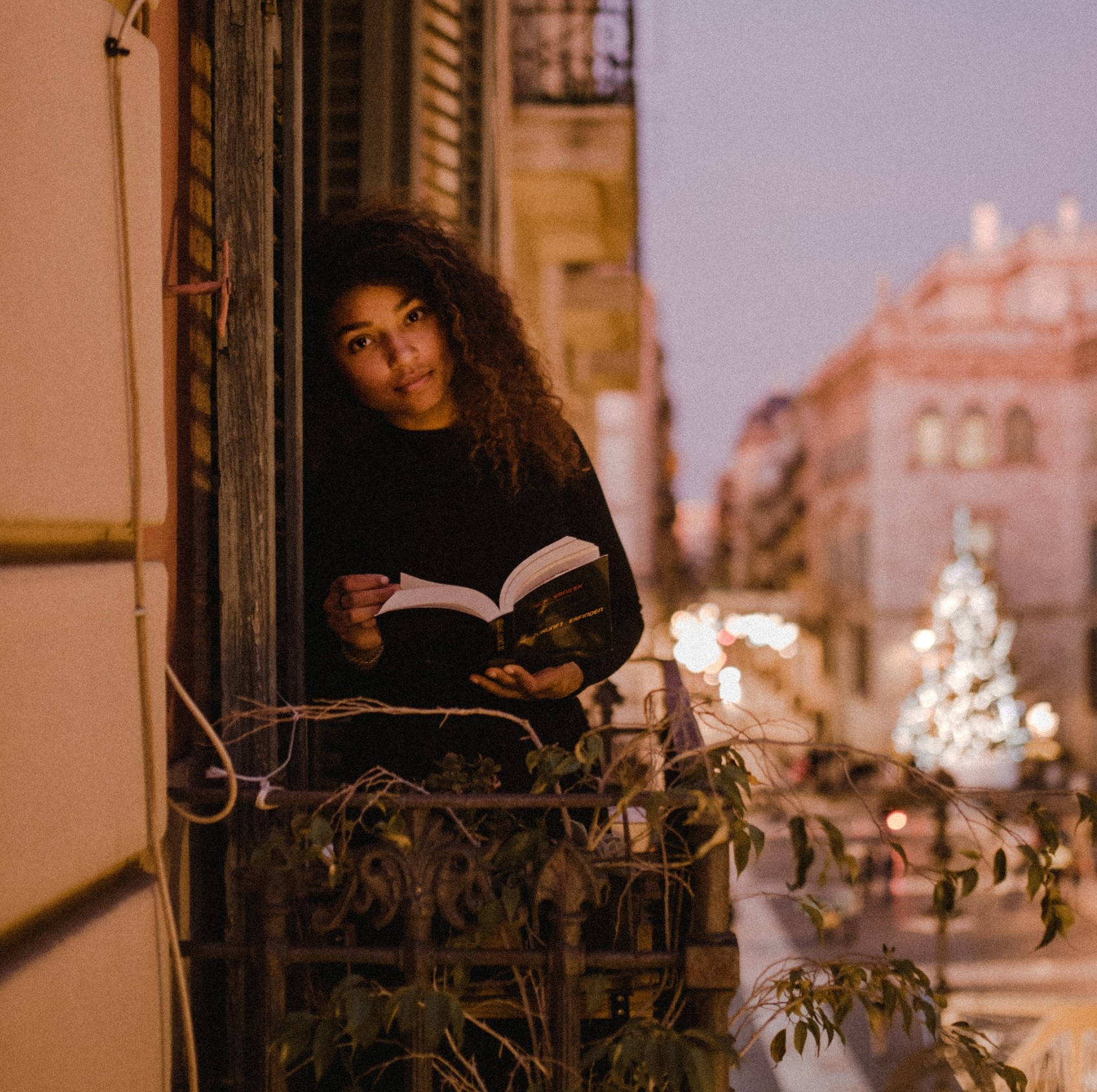 Photo of a woman standing on a balcony reading a book. Reading is part of her evening routine.