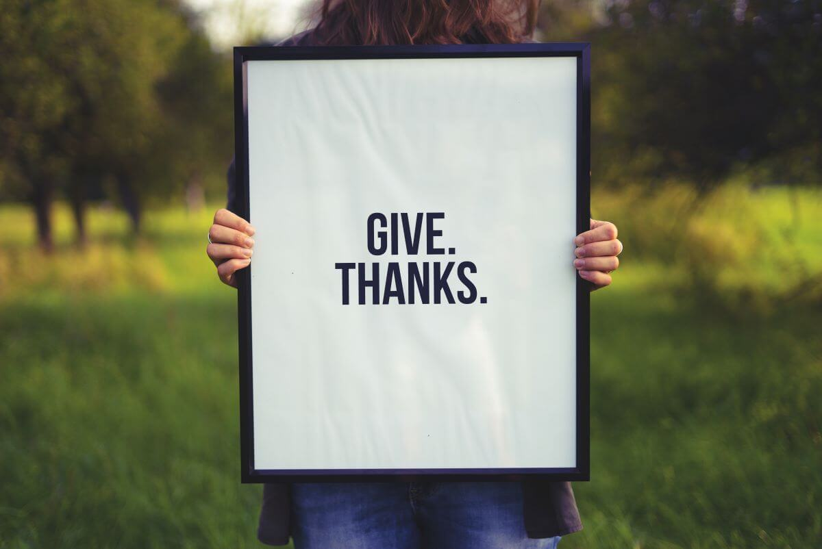 """Photo of a leader holding up a poster that says """"Give Thanks."""""""