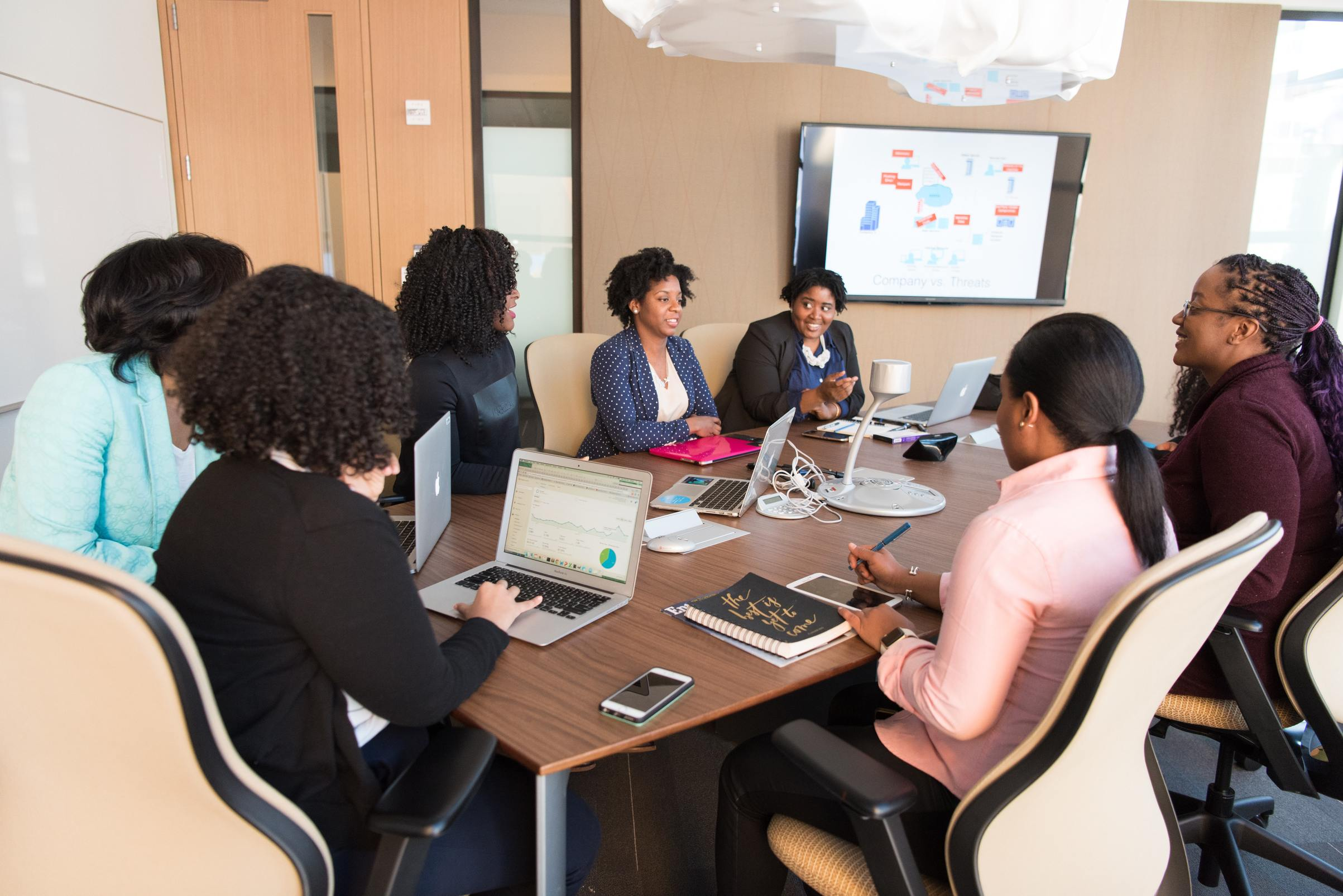 Photo of a group of women sitting at a table brainstorming ways to effectively implement their organizational change plans.