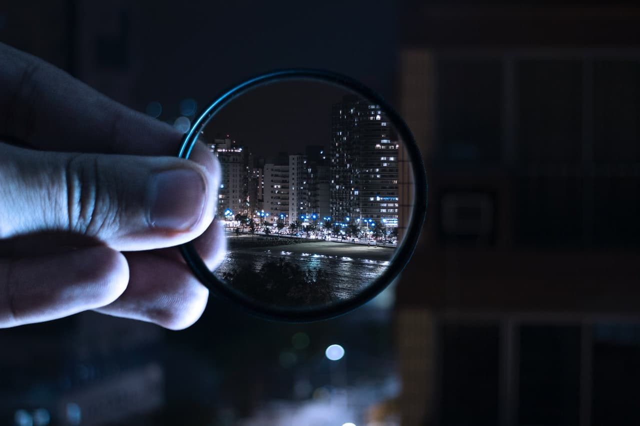 Photo of a magnifying glass being use to focus on a cityscape.