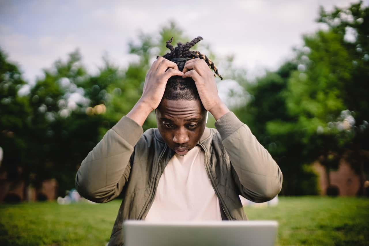 Photo of a man who is stressed while working on a laptop.