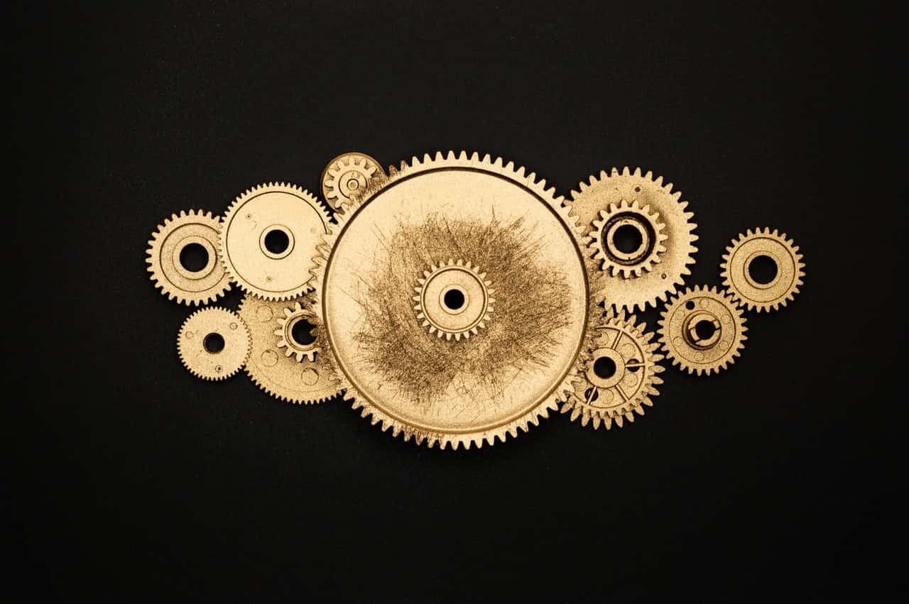 Photo of golden cogs running efficiently on a black background.