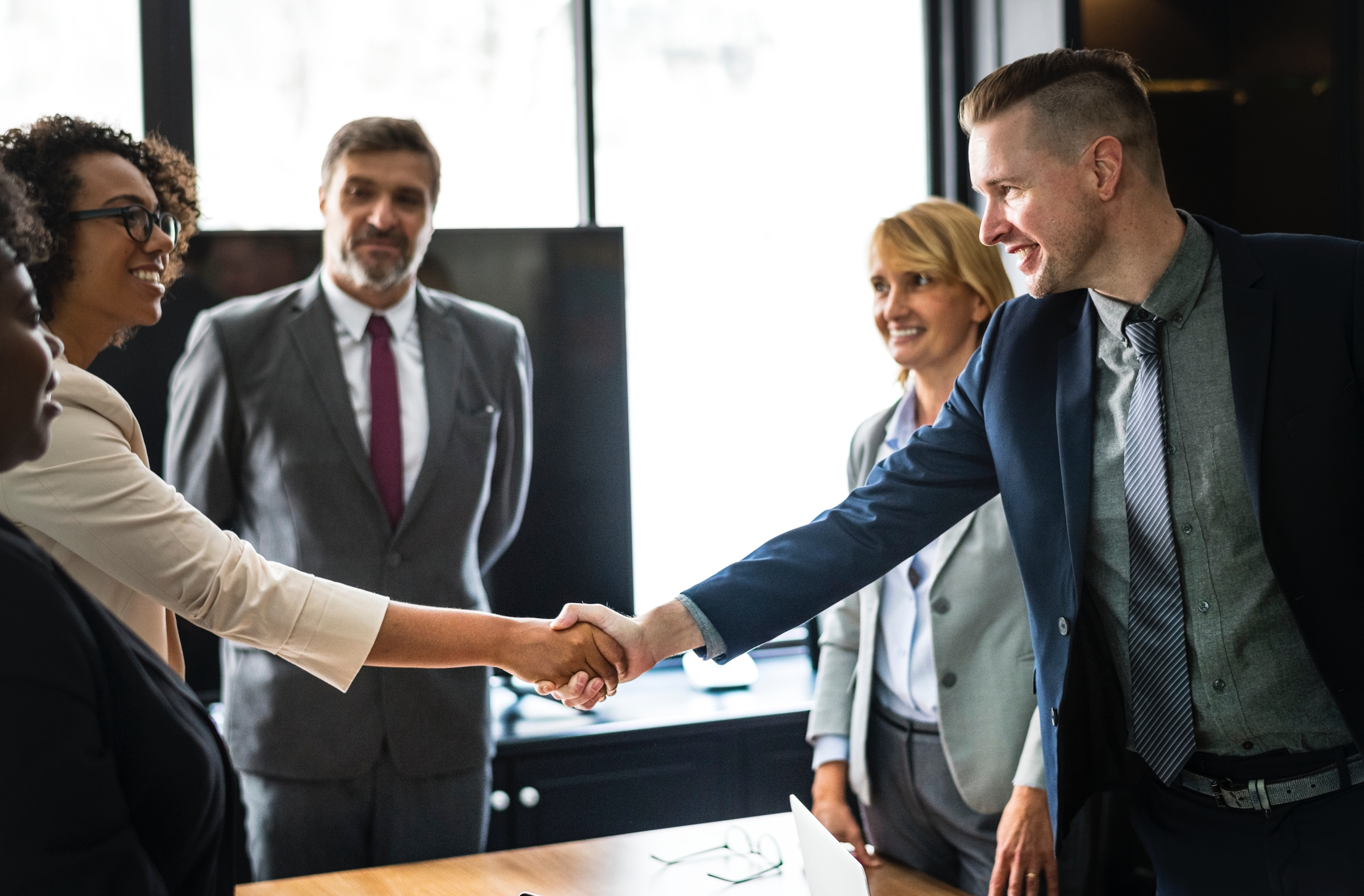 5 business people standing around a table and shaking hands because they are highly satisfied with their client experience.