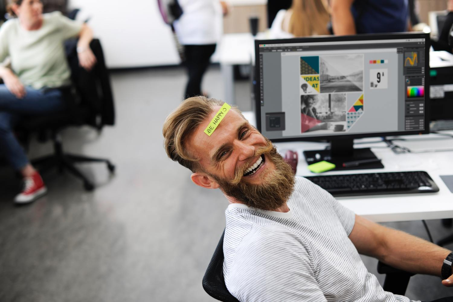 "Photo of man sitting at desk in an office with a sticky note on his forehead that says ""Be Happy"" since he knows it will make him more productive."